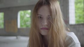 Portrait of caucasian young sad girl sitting in an abandoned building having drug breaking or waiting for support and. Help stock video footage