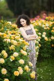 A portrait of Caucasian young woman near yellow roses bush in a rose garden, looking straight to the camera royalty free stock images