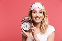 Portrait of caucasian young woman 20s wearing sleeping mask holding alarm clock after awakening stock photography
