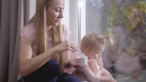 Portrait of caucasian young woman sitting on low windowsill and feeding little blond girl. Pretty mother taking care of stock video footage