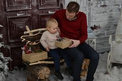 Portrait of caucasin father surprising his little son with Chris. Portrait of caucasian father surprising his little son with Christmas gift at home in the Stock Photo