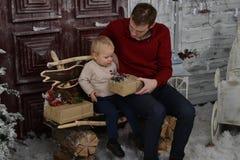 Portrait of caucasin father surprising his little son with Chris. Portrait of caucasian father surprising his little son with Christmas gift at home in the stock photo