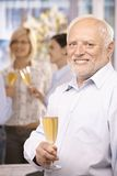 Portrait of celebrating senior businessman. With glass of champagne, smiling at camera Stock Photo