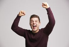 Portrait of a celebrating young white man punching the air royalty free stock photography