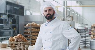 Portrait of charismatic baker man with beard smiling pretty in front of the camera in a commercial kitchen bakery. Background vintage basket with organic stock video