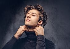 Portrait of a charismatic sensual male in black sweater. Creativ. E personality Royalty Free Stock Photo