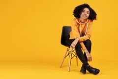 Portrait of charming african american young woman with beautiful smile dressed in casual clothes sitting on the stylish. Chair over yellow background royalty free stock photography