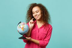 Portrait of charming african girl in casual clothes holding in hands Earth world globe isolated on blue turquoise royalty free stock image
