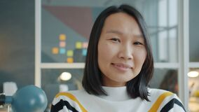 Portrait of charming Asian girl looking at camera then smiling indoors in office