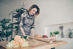 Portrait of charming attractive stylish trendy lady gardener self-employed use table make bouquets clients positive. Content enjoy excited wavy curly hair royalty free stock image