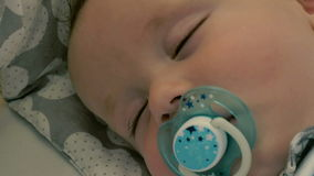 Portrait of charming baby with dummy is sleeping stock footage