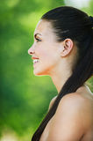 Portrait charming bare woman. Portrait charming woman profile long dark hair bare smiling background green park Royalty Free Stock Photo