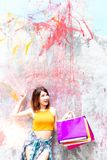 Portrait charming beautiful shopper woman. Attractive beautiful. Girl is pointing finger to copy space and holding shopping bags. Gorgeous woman acts like a stock photos