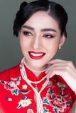 Portrait charming beautiful woman. Attractive beautiful young lady wears cheongsam or Chinese dress with peal necklace. Gorgeous stock image
