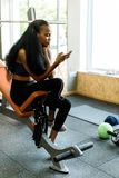 Portrait of charming black young woman with luxury long hair texting on her smartphone in the gym Royalty Free Stock Image