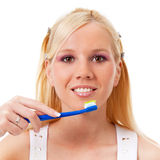 Portrait of a charming blond girl with toothbrush. Against white background royalty free stock image