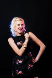 Portrait of a charming blonde woman singing with Royalty Free Stock Photo