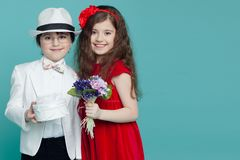 Portrait of a charming boy and girl wearing in white suit and red dress, poses in studio, isolated on blue background. royalty free stock image