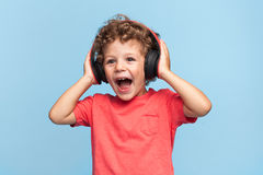 Excited kid posing in headphones. Portrait of charming boy looking away happily while posing in headphones on blue background Stock Images
