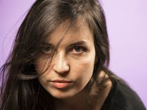 Portrait of a Charming Brunette girl on a Purple Background Royalty Free Stock Images