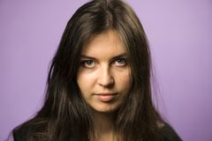 Portrait of a Charming Brunette girl on a Purple Background Royalty Free Stock Photos