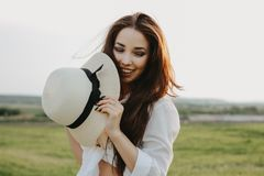 Portrait of charming carefree long hair asian girl in white clothes and straw hat enjoys life in the nature field at sunset. stock photo