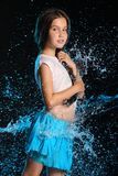 Portrait of a beautiful little girl with bare belly in wet clothes in splashes of water. Portrait of a charming child standing with wet slender body. Pretty Stock Photos