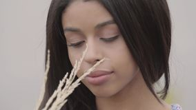 Portrait charming confident carefree African American girl enjoying. Leisure and weekend of a pretty young woman holding. A bunch of grass outdoors. Real people stock video footage