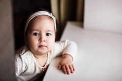 Portrait of charming and curious little girl. Charming and curious little girl looking at camera indoors Stock Photography