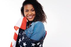 Portrait of a charming curly woman wrapped in US flag. Devoted patriot. The portrait of a beautiful curly brunette posing on a white background while being Stock Photos