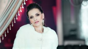 Portrait of charming fashion woman wearing white fur coat posing at vintage background stock footage