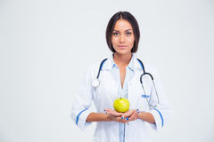 Portrait of charming female doctor holding apple Stock Photography