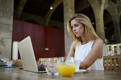 Portrait of a charming female student keyboarding something on net-book while relaxing after lectures in University Royalty Free Stock Image