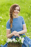Portrait of charming girl with a basket of flower on the lawn Royalty Free Stock Photo