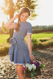 Portrait of charming girl with a basket of flower on the road Royalty Free Stock Image