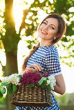 Portrait of charming girl with a basket of flower on the road. Royalty Free Stock Photography
