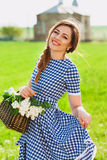 Portrait of charming girl with a basket of flowers at the church Royalty Free Stock Photos