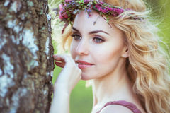 Portrait of charming girl with blond hair, fabulous dress and a tiara in her hair. Near the tree Royalty Free Stock Photo