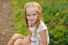 Portrait of charming girl with blonde pigtails, on the grass in Stock Images