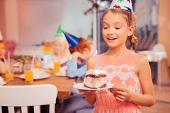 Portrait of charming girl that blowing candle. It is for you. Happy child expressing positivity while looking at her birthday cake stock images