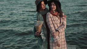Portrait of charming girl in hat and coat at sunset on the background of the autumn sea. friends spend time outdoors. Two cute young women are smiling and stock video footage