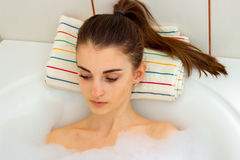 Portrait of a charming girl with a ponytail that rests in a hot tub with foam Stock Photo