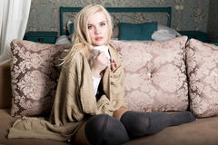 Portrait of charming girl in sweater sitting on a sofa and drinking tea or coffe Stock Images