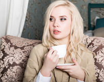 Portrait of charming girl in sweater sitting on a sofa and drinking tea or coffe Stock Photo