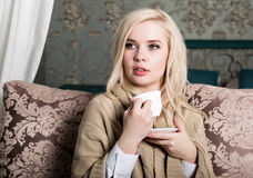 Portrait of charming girl in sweater sitting on a sofa and drinking tea or coffe Royalty Free Stock Images