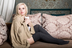 Portrait of charming girl in sweater sitting on a sofa and drinking tea or coffe Stock Photos