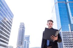 Portrait charming handsome young businessman. Attractive handsome guy is reading projects or paper work in the city or metropolis royalty free stock photo