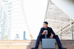 Portrait charming handsome young businessman. Attractive handsome business man is sitting on step and looking at copy space. He i stock photo