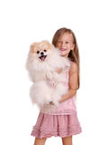A smiling little girl holding a beautiful puppy, isolated on a white background. Childhood, toys and kids concept. royalty free stock photo