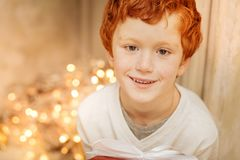 Portrait of charming kid smiling while holding gift Royalty Free Stock Images